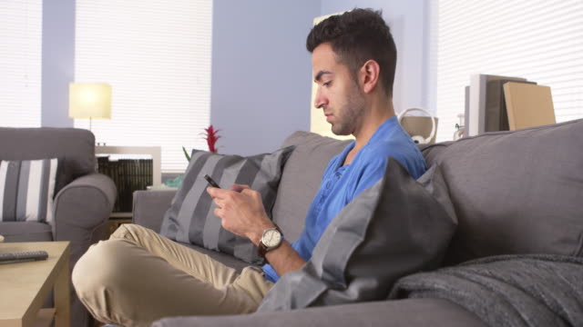 Handsome man texting on couch