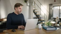 Handsome Man typing on Laptop at modern cosy Home