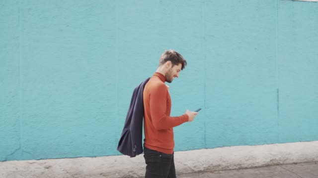 handsome man using mobile phone on the street. - caucasian ethnicity stock videos & royalty-free footage