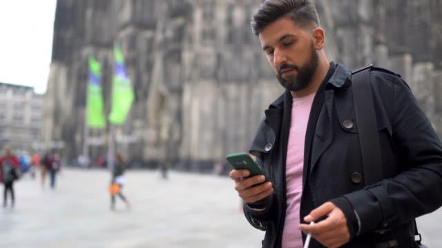 hübscher mann mit smartphone vor dem kölner dom - jacke stock-videos und b-roll-filmmaterial
