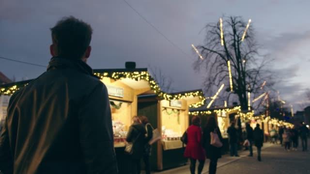 handsome man waist up walking around christmas market - christmas market stock videos & royalty-free footage