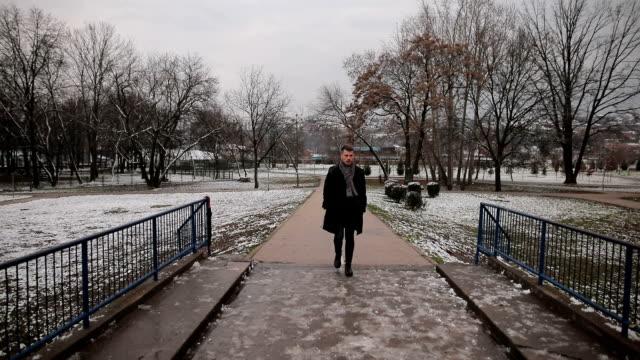 Handsome man walking alone on the bridge