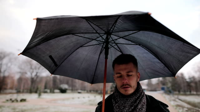 handsome man with an umbrella walking alone - umbrella stock videos and b-roll footage