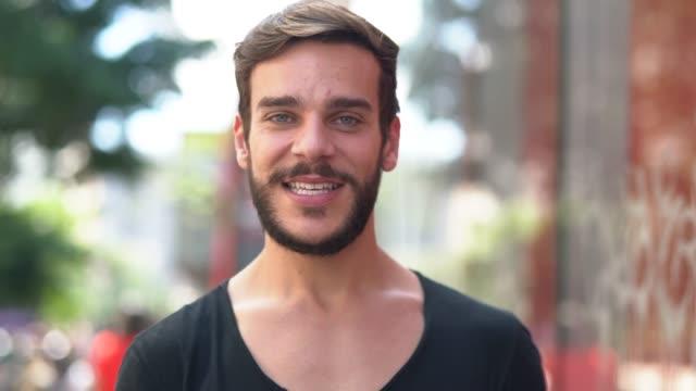 stockvideo's en b-roll-footage met knappe man met zwart shirt en baard portret in de stad - alleen één jonge man
