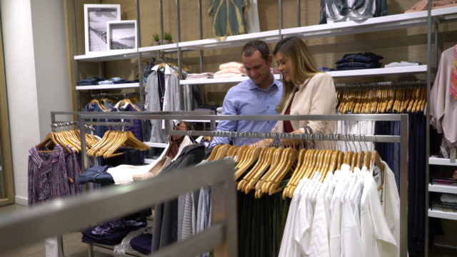 vídeos de stock e filmes b-roll de handsome man with partner choosing women's clothing from a rack while talking - viciado em compras