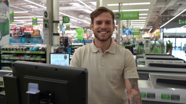 handsome man working as a cashier at a supermarket and then smiling at camera - food and drink stock videos & royalty-free footage