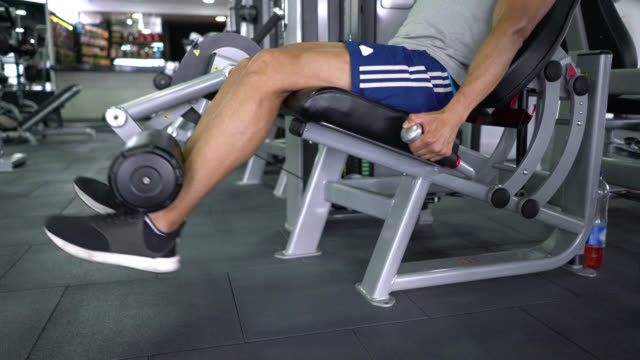 handsome man working out his legs on machine at the gym - exercise machine stock videos & royalty-free footage