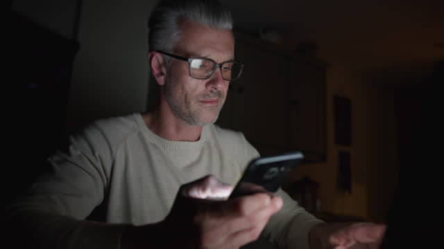 handsome mature man at home working online using laptop and smartphone late at night - urgency stock videos & royalty-free footage