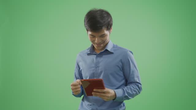 vídeos de stock, filmes e b-roll de homens bonitos tendo um shopping online usando em um tablet em fundo verde. - modelo web