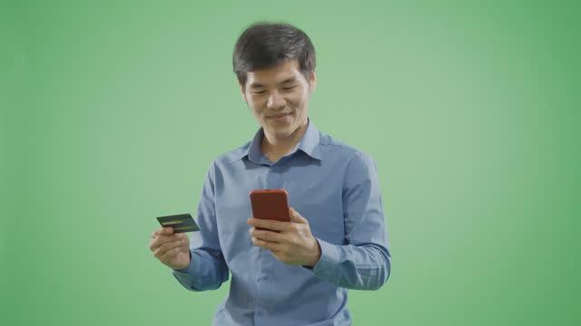 vídeos de stock, filmes e b-roll de homens bonitos tendo uma compra online usando em telefone inteligente em fundo verde. - modelo web