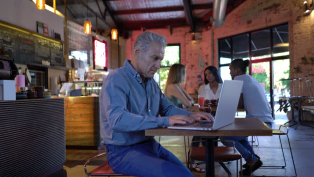 handsome mid adult man working on his laptop at a bakery looking very happy - coffee shop stock videos & royalty-free footage
