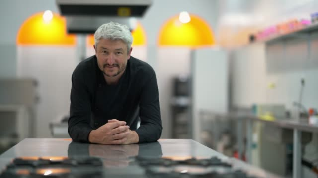 Handsome middle aged chef leaning on a table in the kitchen looking at camera smiling