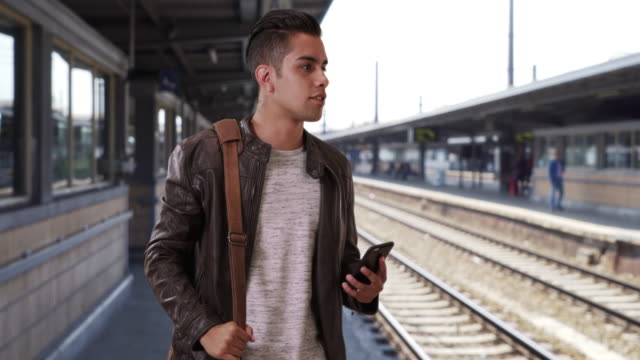 handsome millennial latin male at the train station hailing a ride - 鉄道駅点の映像素材/bロール