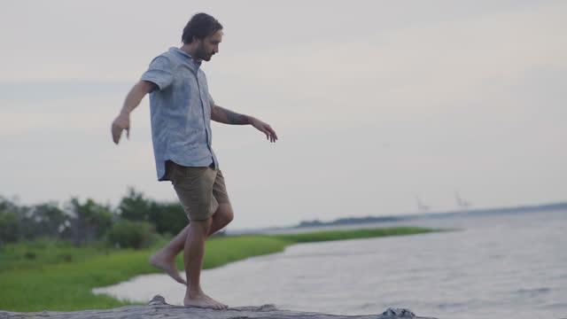 vídeos de stock e filmes b-roll de a handsome millennial man balances while he walks barefoot along a log by the ocean - só um rapaz