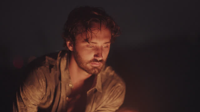 vídeos de stock e filmes b-roll de a handsome millennial man roasts marshmallows over a campfire on the beach - só um rapaz