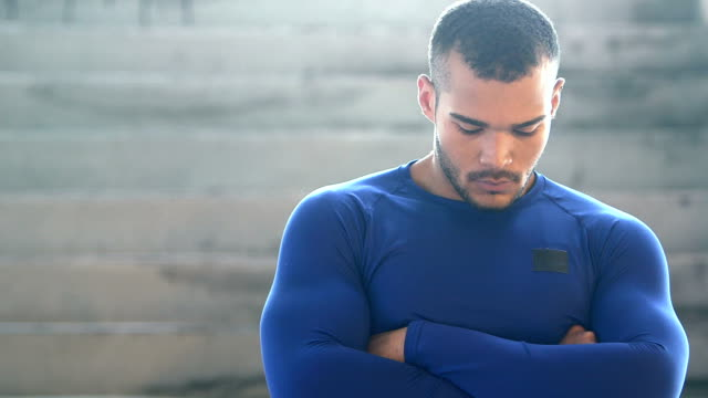 handsome, muscular, mixed race young man, serious - guardare verso il basso video stock e b–roll