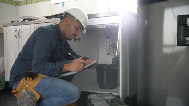 handsome plumber checking a list and pipes of kitchen sink during a home renovation project - examining stock videos & royalty-free footage