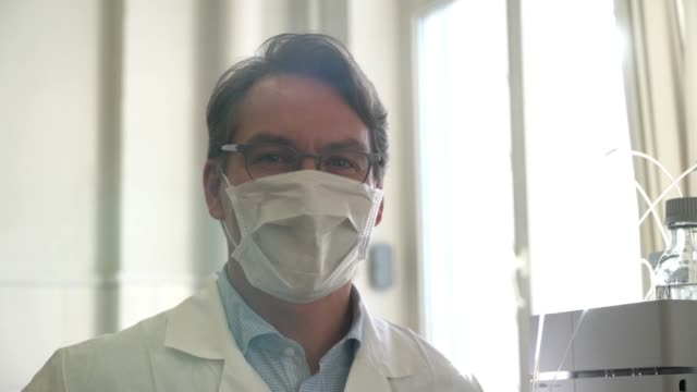 vídeos de stock e filmes b-roll de handsome professional scientist facing camera smiling and then putting on a protective mask - doctor