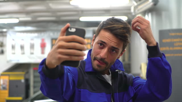 handsome repairman taken selfie for social media in the garage - funky stock videos and b-roll footage