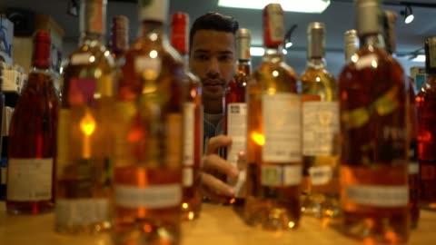 ボトル棚の上を整理するワイナリーでハンサムなセールスマン - ハイチ点の映像素材/bロール