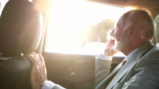handsome senior businessman driving in a car to the office - back seat stock videos & royalty-free footage