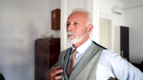 gut aussehend senior geschäftsmann anziehen bevor sie ins büro - europäischer abstammung stock-videos und b-roll-filmmaterial