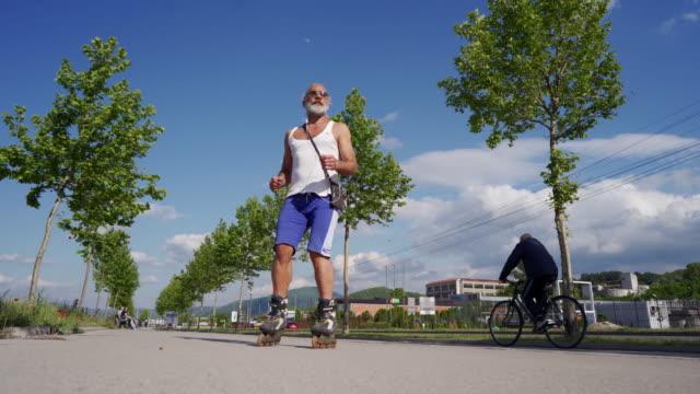 stilig senior man är inline skridskoåkning och spinning på en vacker sommardag - tuff attityd bildbanksvideor och videomaterial från bakom kulisserna