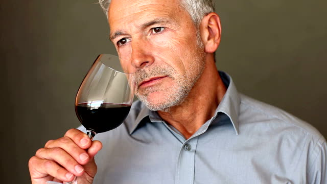 a handsome senior man smelling and then tasting a glass of red wine - smelling stock videos and b-roll footage