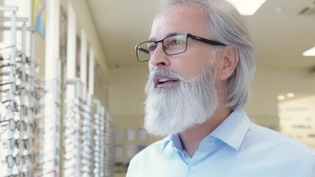 handsome senior man trying on prescription glasses - lens eye stock videos & royalty-free footage