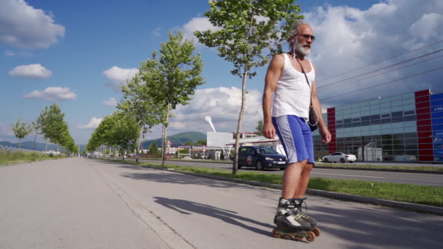 handsome senior man with gray beard is inline skating in slow motion - blade stock videos & royalty-free footage