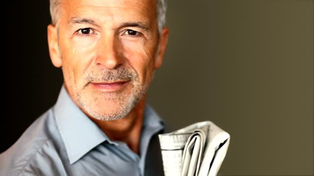 un bell'uomo anziano con giornale - 55 59 anni video stock e b–roll