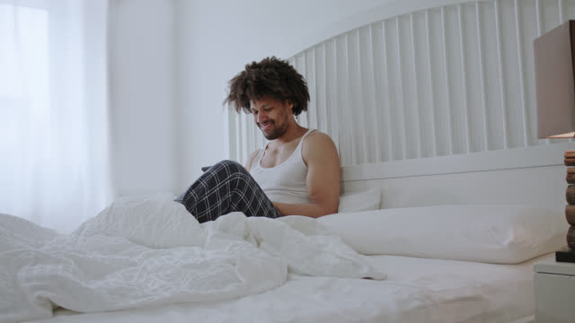 Handsome sexy dark skinned man with long afro hair in his forties sits on white hotel bed while drinking a cup of coffee, blogging and dating using his tablet PC having me-time, right in frame a bedside lamp.