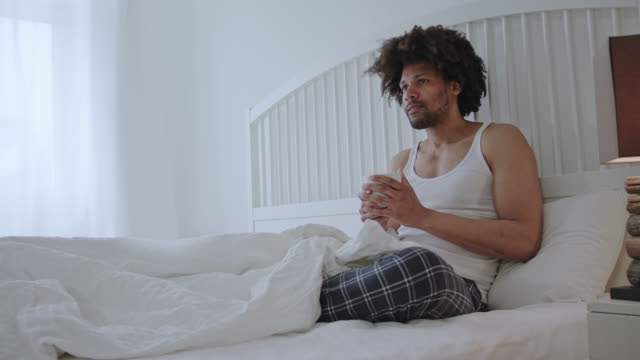 Handsome sexy dark skinned man with long afro hair in his forties sits on white hotel bed enjoying me-time while drinking a cup of coffee - right in frame a bedside lamp.