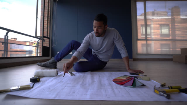 handsome single guy sitting on floor planning while looking at a blueprint of his new home - color swatch stock videos & royalty-free footage