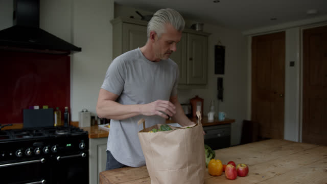 handsome single man unpacking groceries from paper bag at home - paper bag stock videos & royalty-free footage