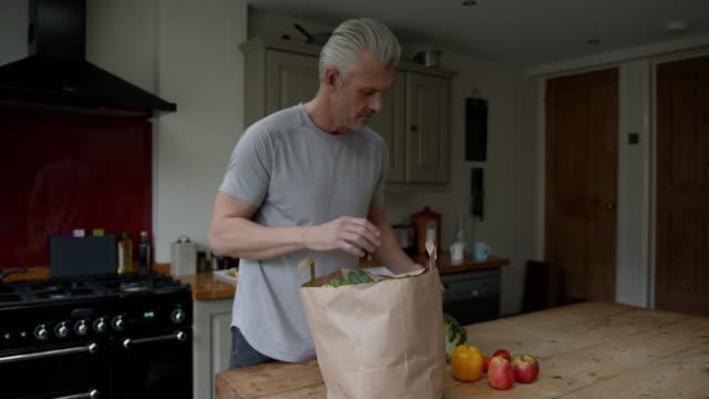 schöne einzelne mann auspacken lebensmittel aus papiertüte zu hause - papiertüte stock-videos und b-roll-filmmaterial