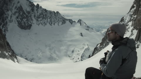 vídeos y material grabado en eventos de stock de handsome skier taking a break, drinking tea, eating apple, looking out over mountain range - hacer un descanso