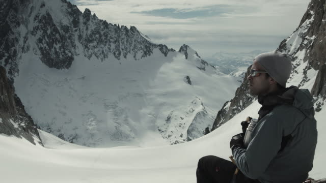 vidéos et rushes de handsome skier taking a break, drinking tea, eating apple, looking out over mountain range - boisson chaude