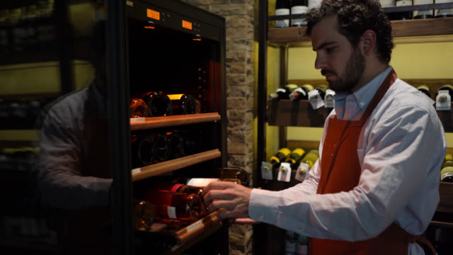 handsome sommelier looking for a special reserve wine in the fridge - wine bar stock videos & royalty-free footage