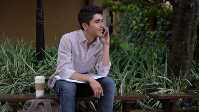 vídeos y material grabado en eventos de stock de estudiante guapo tomando un descanso de estudiar hablando por su teléfono mirando muy feliz - person in further education