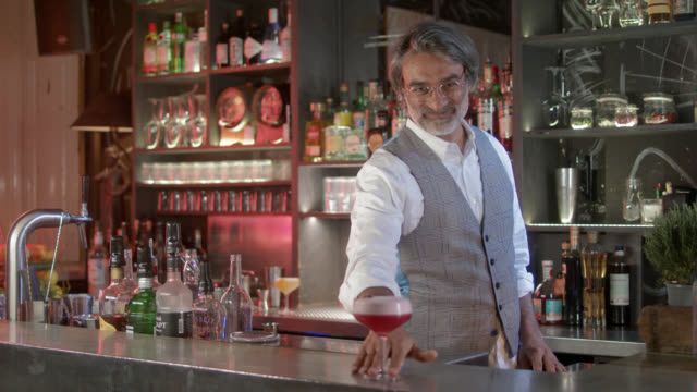 vídeos de stock e filmes b-roll de handsome, stylish bartender and owner of his own trendy, moody, city bar in his early 50s  - proud of his own small business. - qualidade