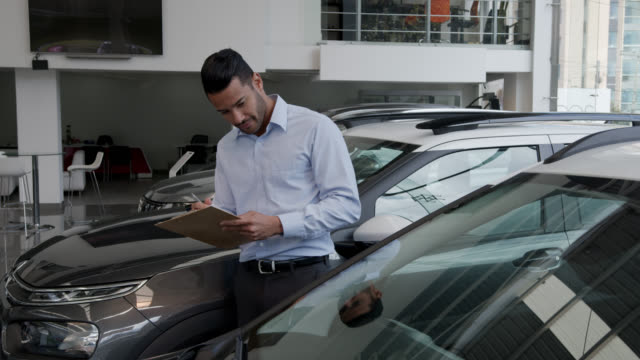 handsome supervisor checking a car at a dealership taking notes on document using a clipboard - examining stock videos & royalty-free footage