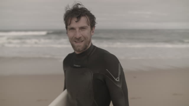 Handsome surfer looking into camera, smiling after going surfing