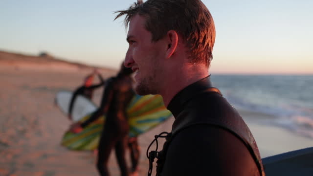 Handsome surfer standing on the beach with group of friends, laughing