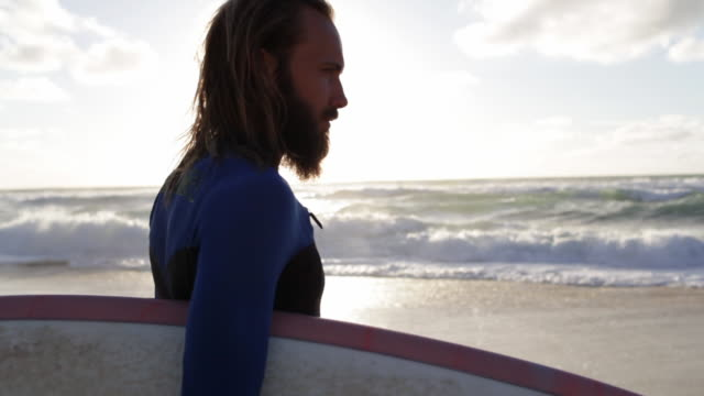 vídeos y material grabado en eventos de stock de handsome surfer with surfboard looking out over waves and toward horizon on beach in france - anticipation