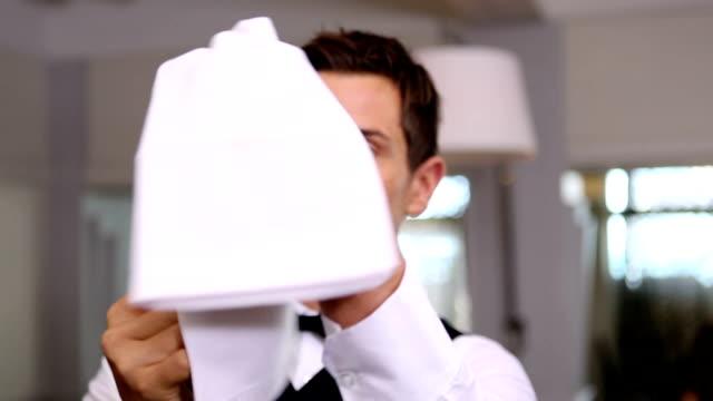 Handsome waiter polishing wine glass
