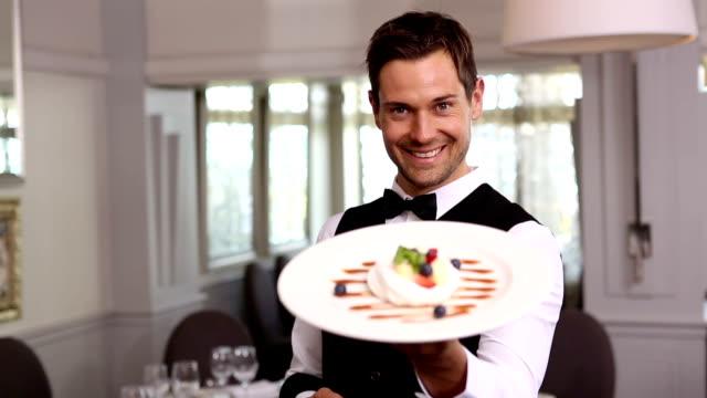Bello cameriere, mostrando un dessert piatto