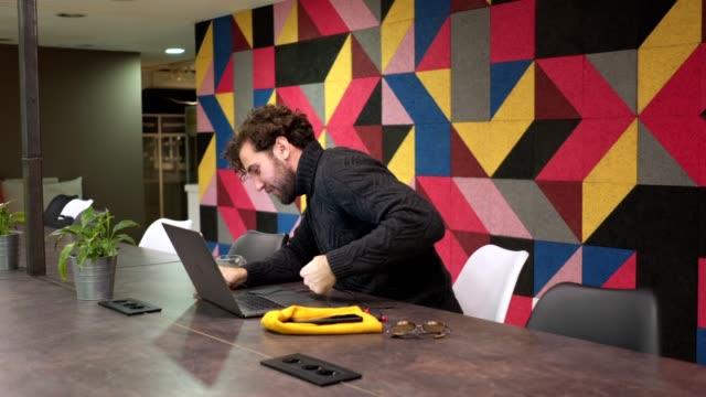 vidéos et rushes de vidéo beau jeune architecte chat sur son ordinateur portable pendant que vous prenez une pause café - utiliser un ordinateur portable