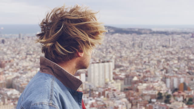 Handsome young blond man looking at cityscape