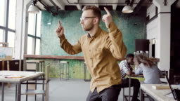 Handsome young businessman doing victory dance about successful achievement. Happy male at modern trendy office
